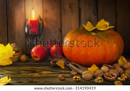 Halloween - pumpkin, nuts, apples by candlelight in autumn colors - stock photo