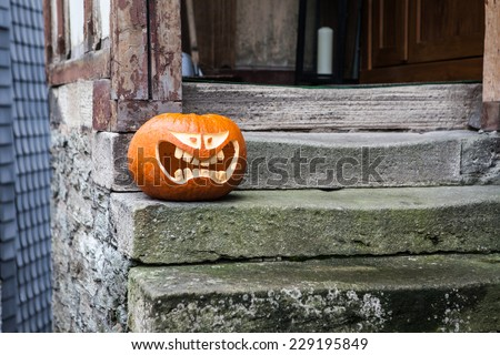 Halloween pumpkin on a stone staircase. The photograph shows a decorative Halloween pumpkin on a stoop of a particular stone house in a rural area - stock photo