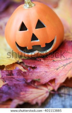 Halloween pumpkin on autumnal leaves - stock photo