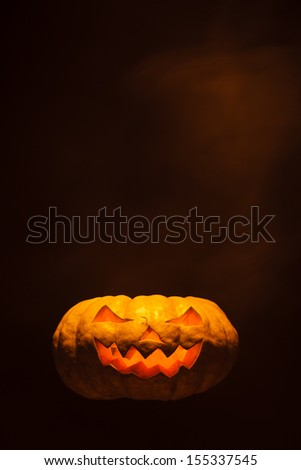 Halloween pumpkin on black background with copy space above it - stock photo