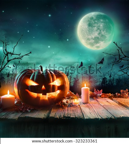 Halloween Pumpkin On Wooden Plank With Candles In A Spooky Night  - stock photo