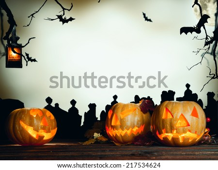 Halloween pumpkin on wooden planks. Cemetery grave stones on background