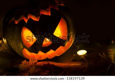 Halloween pumpkin with candles and leaves - stock photo