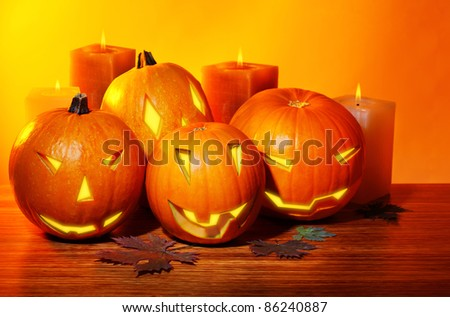 Halloween pumpkin with candles, warm autumn holiday background, traditional jack-o-lantern, night party decoration - stock photo