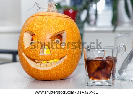 Halloween pumpkin with carved face and glass of whiskey with ice on holiday table - stock photo
