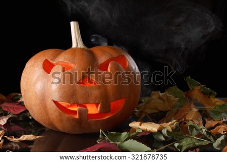 Halloween pumpkin with fallen leaves, a terrible fire, smoke and reflections.on black background - stock photo