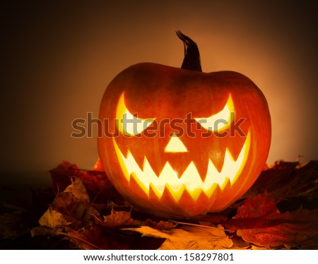Halloween pumpkin with leafs on orange background - stock photo