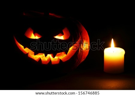 Halloween pumpkin with scary face and burning candle on black background - stock photo