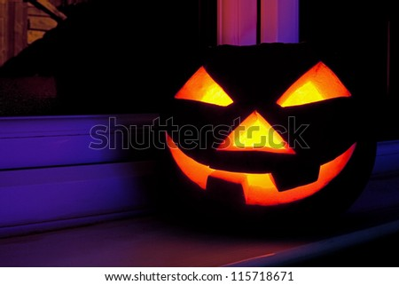 Halloween pumpkin with scary face on the window at night - stock photo