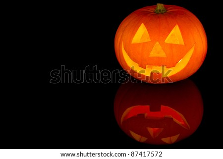 Halloween pumpkin with scary face with reflection on black glass - stock photo