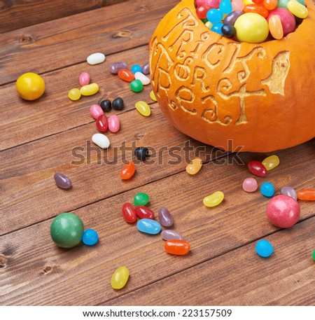 Halloween pumpkin with the words trick or treat carved over its surface and filled with multiple sweets and candies, composition over the wooden board background - stock photo