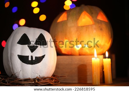 Halloween pumpkins and candles on table on dark color background with multicolor lights - stock photo
