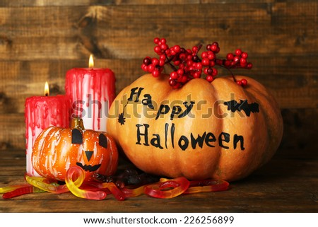 Halloween pumpkins and candles on wooden table background - stock photo