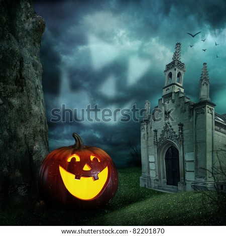 Halloween pumpkins and cemetery chapel at night - stock photo