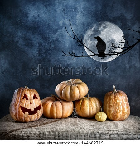 Halloween pumpkins and crow on the branch at full moon and textured dark background - stock photo