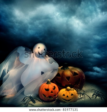 Halloween pumpkins and ghost at night - stock photo