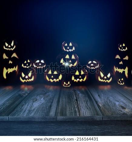 Halloween pumpkins in a dark eerie background and wood floor - stock photo