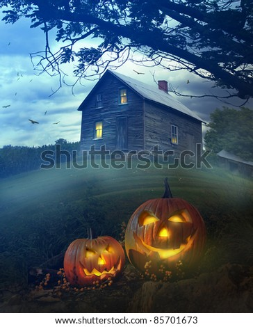 Halloween pumpkins in front of a Spooky house - stock photo