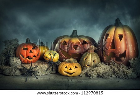 Halloween pumpkins on a wooden desk at night - stock photo