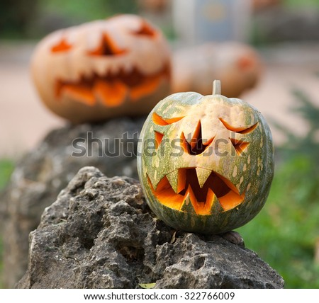 Halloween pumpkins outdoor. Creepy carved pumpkin faces in park. Focus on foreground - stock photo