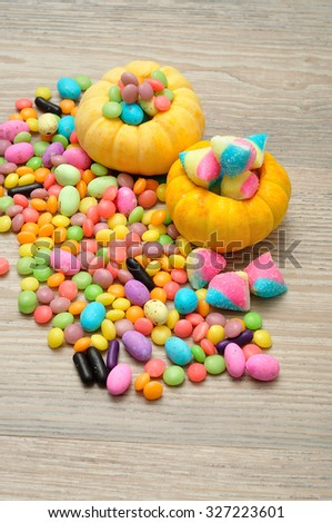 Halloween pumpkins that is hollowed out and filled with multiple sweets and candies, composition over a wooden background - stock photo