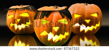 Halloween pumpkins with black fringes and carved faces lit from inside - stock photo