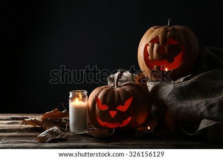 Halloween pumpkins with candle on brown wooden table - stock photo