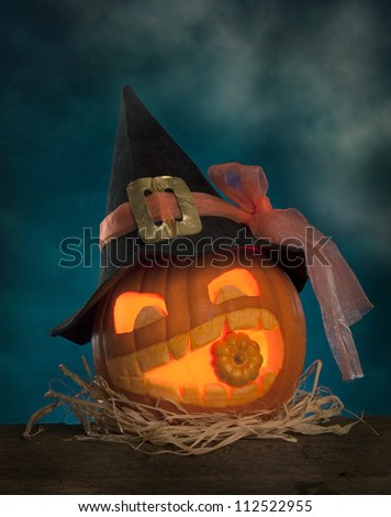 Halloween pumpkins with witch hat on a wooden desk - stock photo