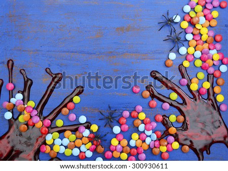 Halloween rustic blue wood background with bloody hand prints, candy and spiders, with copy space for your text here.  - stock photo