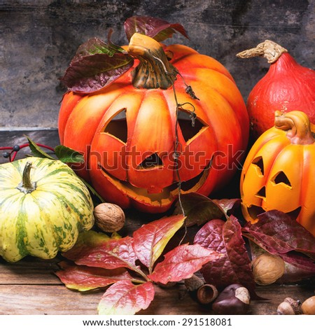 Halloween's pumpkins with autumn leaves on wooden table. Square image with selective focus - stock photo