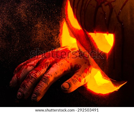 Halloween scare or fear: Carved halloween pumpkin with a bloody hand. The spooky and creepy fall tradition of Halloween - stock photo
