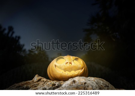 Halloween scary pumpkin jack-o-lantern with a smile on a rock from bottom perspective template illustration from the darkness - stock photo