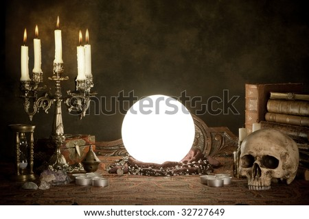 Halloween scene of a crystal ball, skull and candles - stock photo