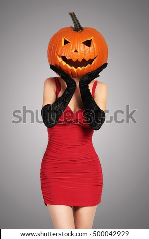 Halloween. Sexy lady in red with big pumpkin on her head.