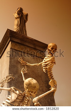 Halloween skeleton with statue - stock photo