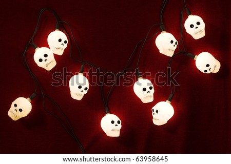 Halloween skull shaped lights against dark red textured wall. Also go for Day of the Dead. - stock photo