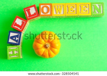 Halloween spelled with alphabet blocks with pumpkin against a green  background