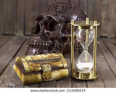 Halloween still life with creepy skull, sandglass and box - stock photo