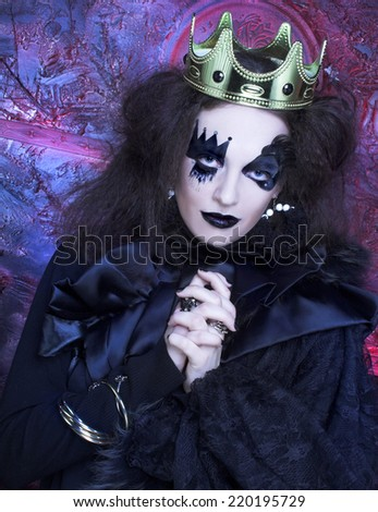 Halloween: The Mad queen. Young woman with creative visage and in crown - stock photo