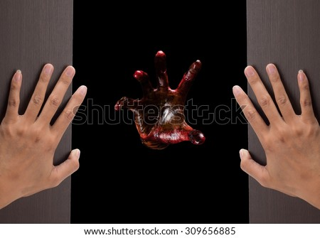 Halloween theme:Two woman hands opening a wooden door with bloody hands  background.film filter effect. - stock photo