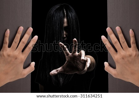 Halloween theme:Two woman hands opening a wooden door with ghost girl on black background.film filter effect.