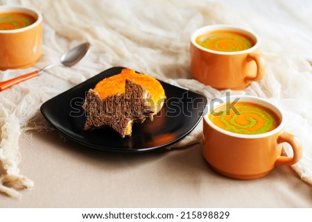 Halloween themed meal. Cutout grilled cheese sandwiches on pumpernickel and orange colored bread. Tomato soup with pesto swirls.