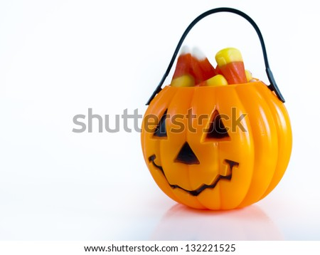 Halloween treat bag filled with candy corn candies on white background. - stock photo
