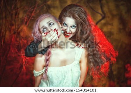Halloween vampire and her victim - stock photo