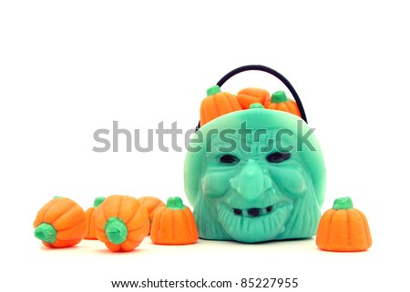 Halloween witch and a pile of scattered gummy pumpkin candies against a white background - stock photo