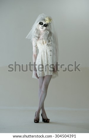 Halloween witch. Beautiful woman wearing santa muerte mask and wedding dress posing full length - stock photo
