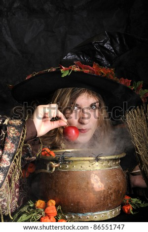 Halloween witch cooking in a copper cauldron