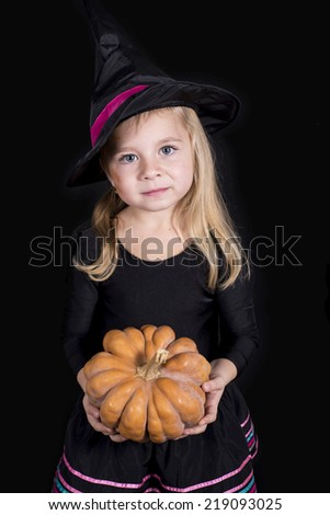 Halloween witch holding a pumpkin - portrait of little girl in black hat and black clothing on black background - stock photo
