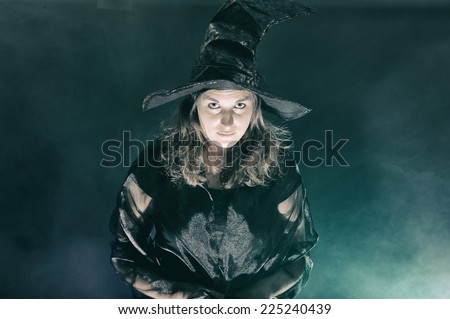 Halloween witch on smoke green and purple background - stock photo