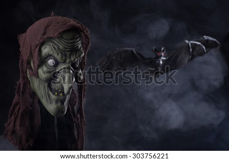 Halloween witch prop with a bat and smoky background - stock photo